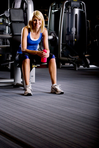 Portrait of smiling woman with water bottle sitting on exercise equipment in health clubの写真素材 [FYI02852781]