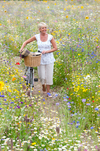 Woman pushing bicycle on path through wildflowers in fieldの写真素材 [FYI02852795]