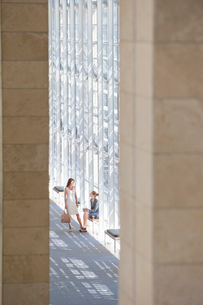 Businesswomen talking in lobby of modern officeの写真素材 [FYI02852803]