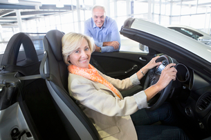 Portrait of smiling couple looking at convertible in car dealership showroomの写真素材 [FYI02852805]