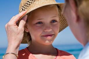 Senior woman placing straw sun hat on granddaughter's head, girl (8-10) smiling (differential focus)の写真素材 [FYI02852823]