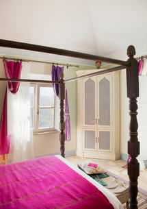 Four poster bed with purple bedding in bedroomの写真素材 [FYI02852824]