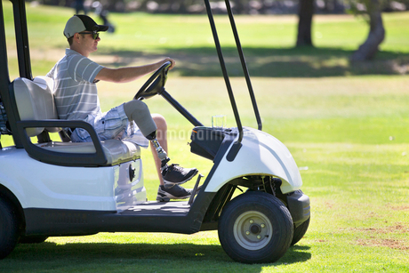 Male Golfer With Artificial Leg Driving Buggy On Golf Courseの写真素材 [FYI02852833]