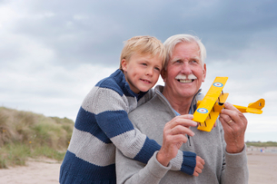 Grandfather And Grandson Playing With Model Aeroplane On Beachの写真素材 [FYI02852849]