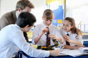 Teacher teaching high school students assembling robot in science classの写真素材 [FYI02852856]