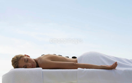 A young woman receiving a hot stone holistic treatmentの写真素材 [FYI02852891]