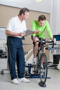 Sports scientist with digital tablet monitoring cyclist on exercise bike in laboratoryの写真素材 [FYI02852908]