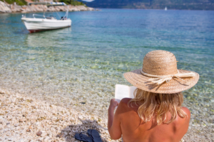 Woman in sun hat reading book on sunny beachの写真素材 [FYI02852911]
