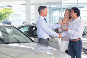 Salesman giving couple car keys in car dealership showroomの写真素材 [FYI02852912]