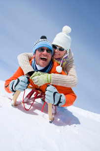 Smiling couple riding through snow on sled togetherの写真素材 [FYI02852913]