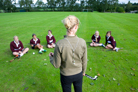 Coach standing before teenage girl field hockey teamの写真素材 [FYI02852917]