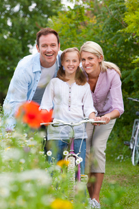 Portrait of smiling family with bicycle in fieldの写真素材 [FYI02852935]