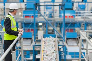 Businessman watching plastic on conveyor belt in recycling plantの写真素材 [FYI02852940]