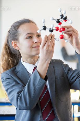 Smiling high school student examining molecule model in science classの写真素材 [FYI02852956]