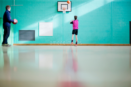 Coach watching high school basketball player in gymの写真素材 [FYI02852972]