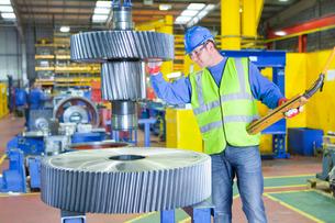 Worker inspecting gear wheels in factoryの写真素材 [FYI02852977]