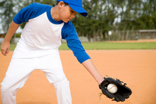 Boy catching baseball in gloveの写真素材 [FYI02852990]