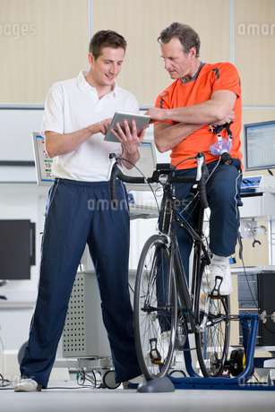 Sports scientist and cyclist on exercise bike looking down at digital tablet in laboratoryの写真素材 [FYI02852996]