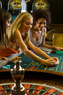 Young woman collecting pile of gambling chips at roulette table, smilingの写真素材 [FYI02852999]