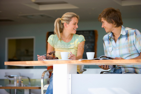 Teenage couple (16-18) sitting in cafe, smiling at each otherの写真素材 [FYI02853007]