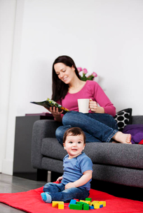 A mother relaxing on a sofa with a magazine and hot drink, baby playing on the floorの写真素材 [FYI02853031]