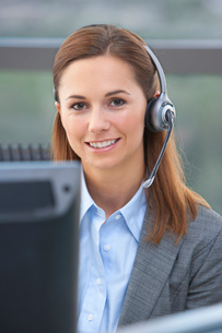 Close up portrait of smiling businesswoman wearing headsetの写真素材 [FYI02853057]