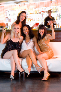 Medium group of young women with drinks in bar, smiling, portraitの写真素材 [FYI02853068]