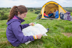 Girl looking down at map near friends and tent in rural fieldの写真素材 [FYI02853072]