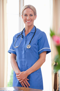 Portrait of smiling home caregiver wearing uniform and stethoscopeの写真素材 [FYI02853077]