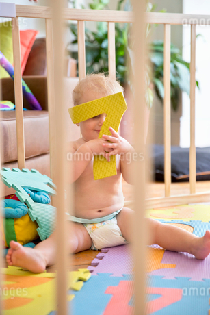 Smiling Baby Boy In Wooden Playpen At Homeの写真素材 [FYI02853088]
