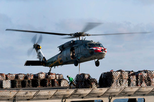 An MH-60S Sea Hawk lifts cargo from the fast combat supportの写真素材 [FYI02853123]