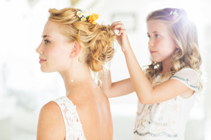 Bridesmaid helping bride with hairstyle in domestic roomの写真素材 [FYI02853270]