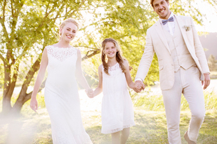 Bride, bridegroom and bridesmaid walking in domestic gardenの写真素材 [FYI02853284]