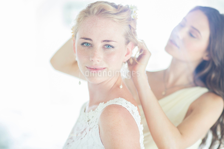 Bridesmaid helping bride with hairstyle in domestic roomの写真素材 [FYI02853293]