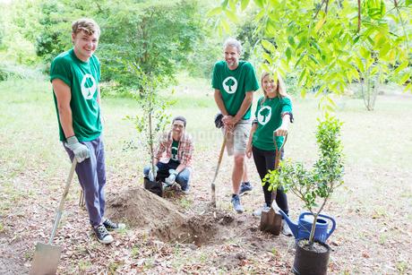 Portrait of confident environmentalist volunteers planting new treeの写真素材 [FYI02853295]