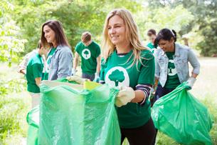 Smiling environmentalist volunteer picking up trashの写真素材 [FYI02853310]
