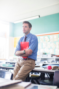 Portrait of male teacher leaning at desk in classroomの写真素材 [FYI02853315]