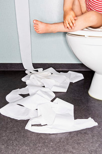 Low section of girl sitting on toilet bowl with paper on floorの写真素材 [FYI02853342]