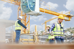 Foreman guiding construction workers below crane at construction siteの写真素材 [FYI02853367]
