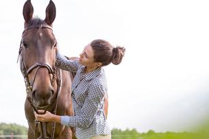 Woman petting horseの写真素材 [FYI02853371]