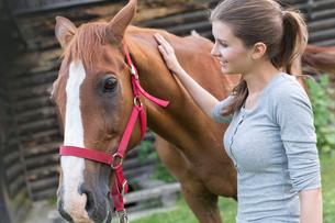 Woman petting horseの写真素材 [FYI02853372]