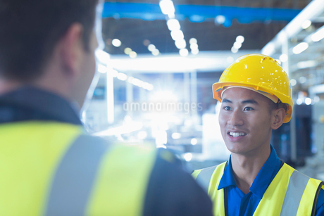 Workers in reflective clothing talking in factoryの写真素材 [FYI02853374]