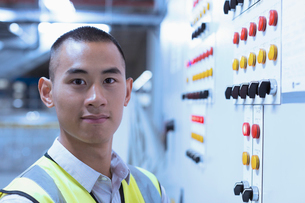 Portrait confident worker at control panel in factoryの写真素材 [FYI02853377]