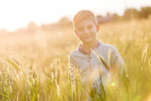 Portrait smiling boy in sunny rural wheat fieldの写真素材 [FYI02853385]