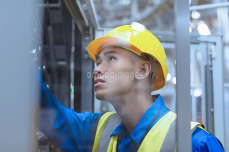 Worker in hard-hat examining machinery in factoryの写真素材 [FYI02853405]