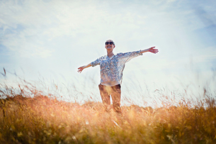 Carefree senior woman running with arms outstretched in sunny fieldの写真素材 [FYI02853429]