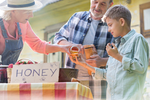 Grandparents and grandson tasting and selling honey at farmer's market stallの写真素材 [FYI02853456]