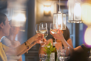 Women friends toasting white wine glasses dining at restaurant tableの写真素材 [FYI02853489]