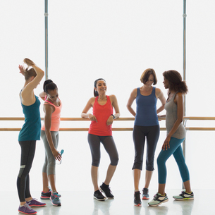Smiling women talking and drinking water at barre in exercise class gym studioの写真素材 [FYI02853514]
