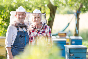 Portrait confident beekeepers in protective hats near hivesの写真素材 [FYI02853542]